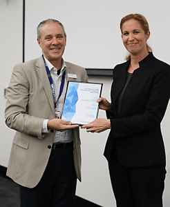 Dr France Milat receiving her award from Monash Health CEO, Mr Andrew Stripp.