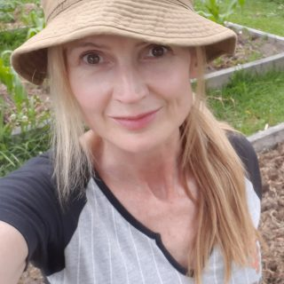 Imelda, wearing a hat and working in the garden.