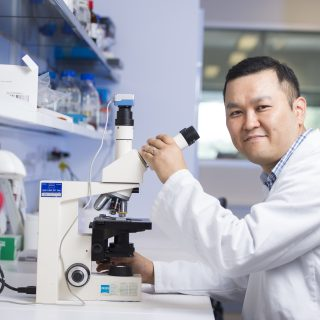 Dr Joohyung Lee, Honorary Research Associate, working at the lab bench and using a microscope to assist with his medical research