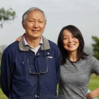 Dr Jun Yang standing with her father in a park
